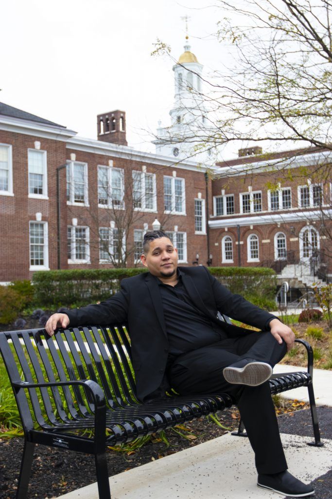 Angel wears a dark blue suit and sits on a bench outside Bunce Hall