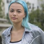 Rowan University student with blue hair wearing a silver silk jacket standing outside Robo