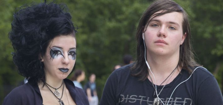 Concetta Davis (left), dressed in goth style with all black clothing and eye makeup stands next to her friend wearing a Disturbed shirt.