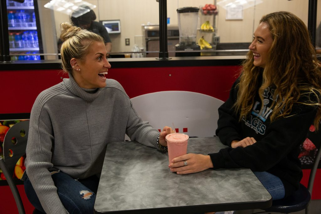 Vanessa and her friend sitting at a table drinking a pink smoothie