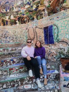 Two students sitting on mosaic covered stairs.