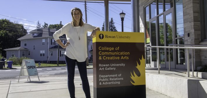 student outside communications building at Rowan University, hand on hip and other leaning on the building sign