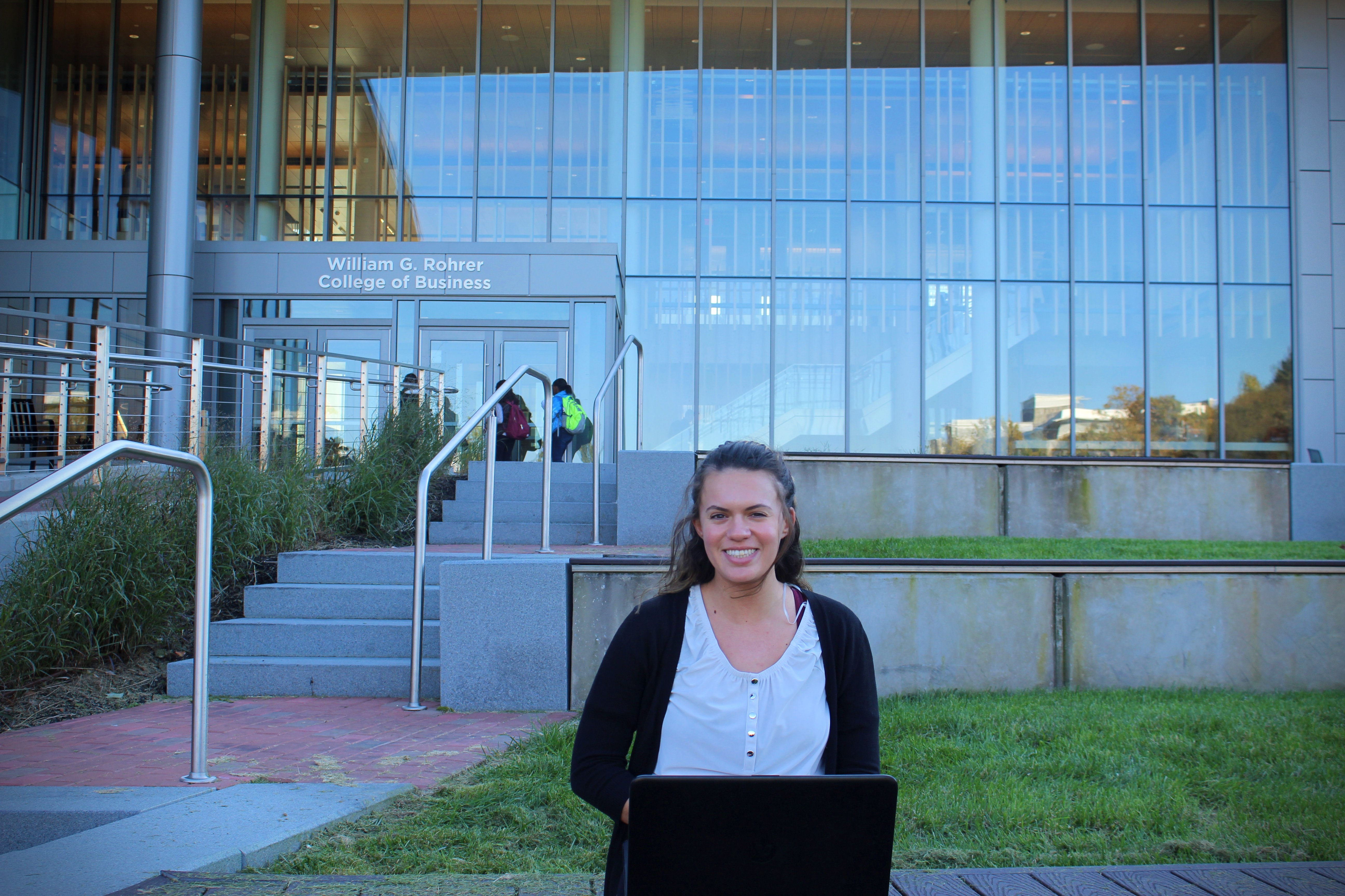 Elizabeth sitting outside of Rowan's William G. Rohrer College of Business with her laptop.