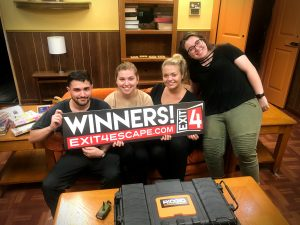 "four friends hold a ""winners"" sign at Exit 4 Escape Room"