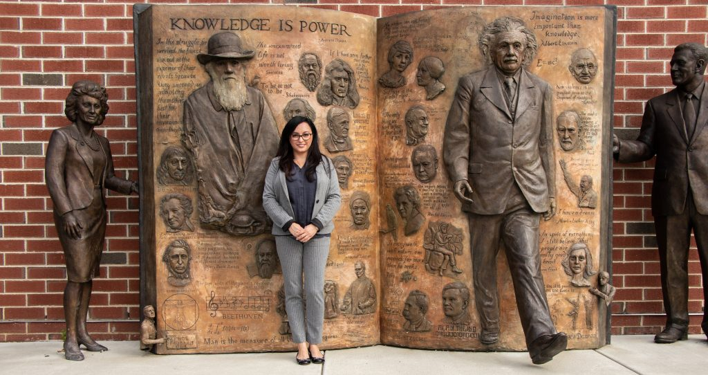 business woman standing in front of bronze statue of famous scientists and philosophers