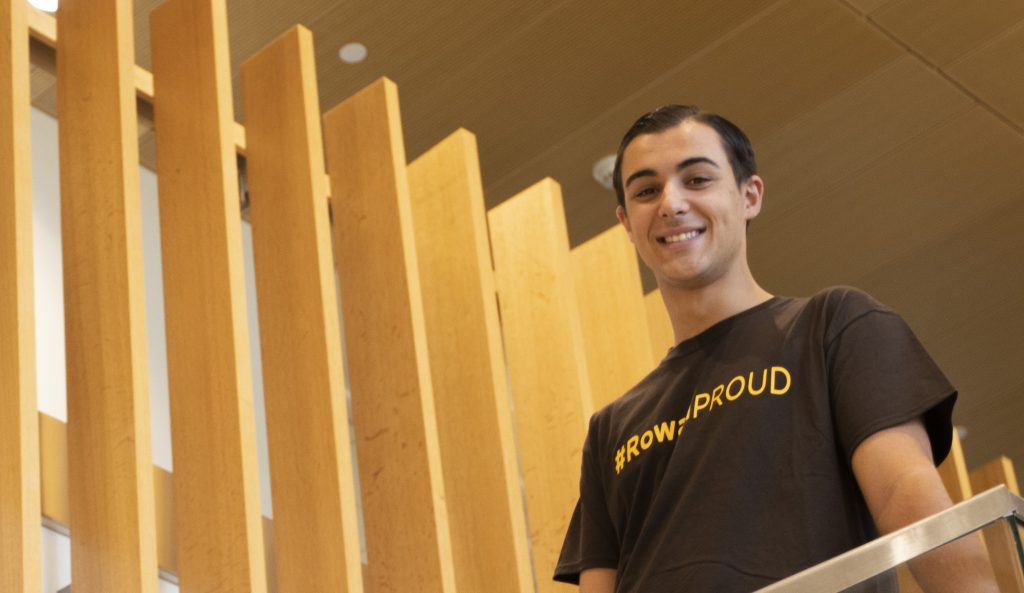 "Dan Ryan stands in his ""Rowan Proud"" shirt on the stairs in the Business Hall at Rowan University."