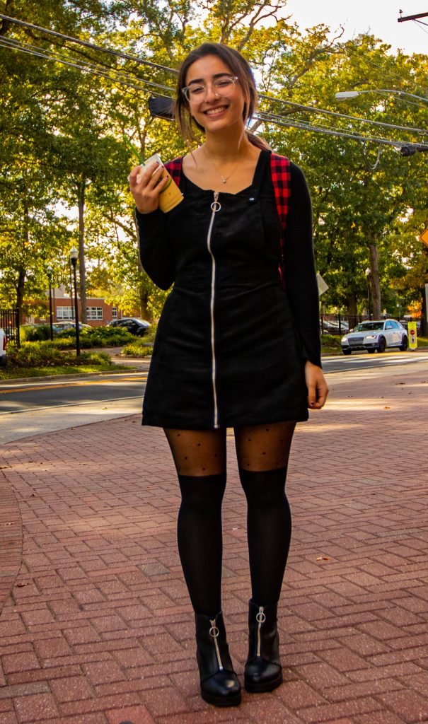 Gabi stands holding a Starbucks drink, wearing knee-high black boots, a black dress and a red and black plaid backpack