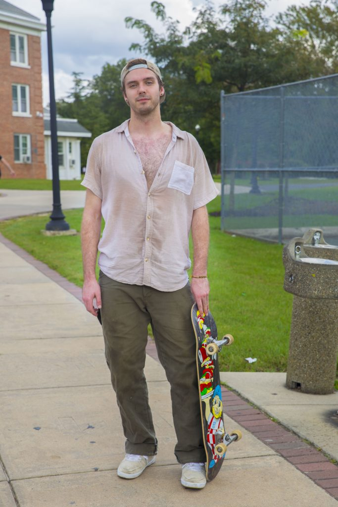 Rowan University student wearing a backward hat standing with his skateboard