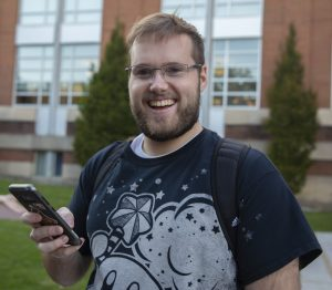 Max, a student wearing a backpack and kirby shirt, plays pokemon go near the library