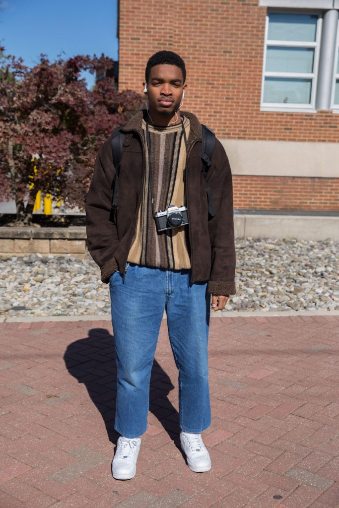 Quinton Palms stands outside wearing a brown jacket, brown striped sweater, jeans and with a camera around his neck.
