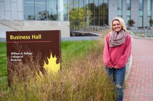 Kylie outside of Rowan Business Building standing next to business hall sign
