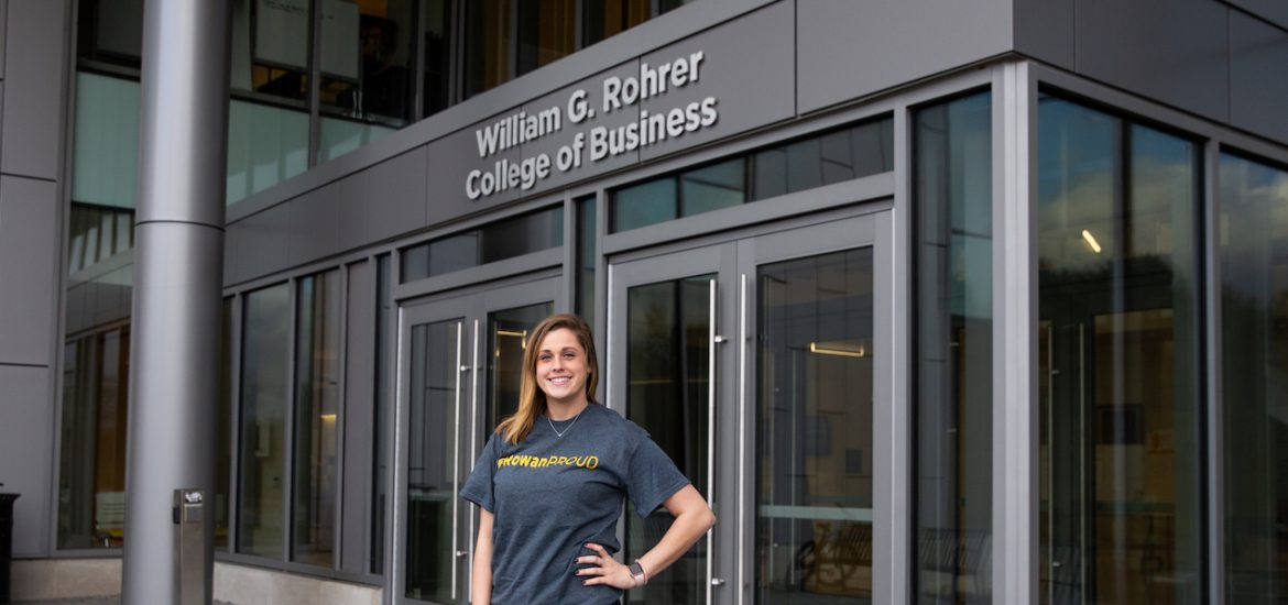 Rachel outside business building with silver sign in background saying Rohrer College of Business