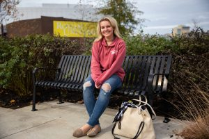 Kylie sitting on bench outside Rowan Wilson Hall