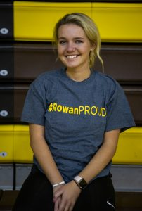 Kylie in her #ROWANproud shirt sitting inside on bleachers
