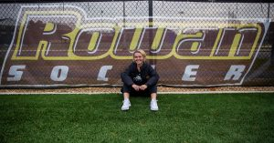 Kylie outside on soccer field in front of Rowan Soccer sign