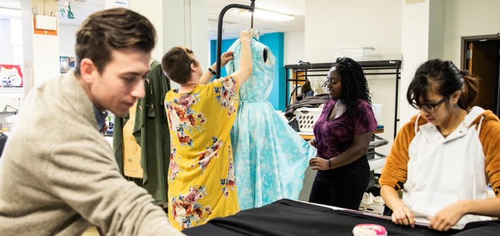 Three students and the costume shop professor work together pinning curtains