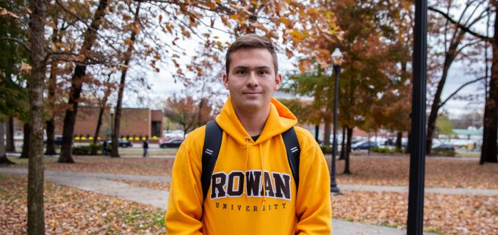 student in Rowan hoodie outside in front of fall leaves and trees