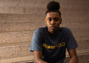 Lawrance in #ROWANproud shirt sitting on the steps inside James Hall