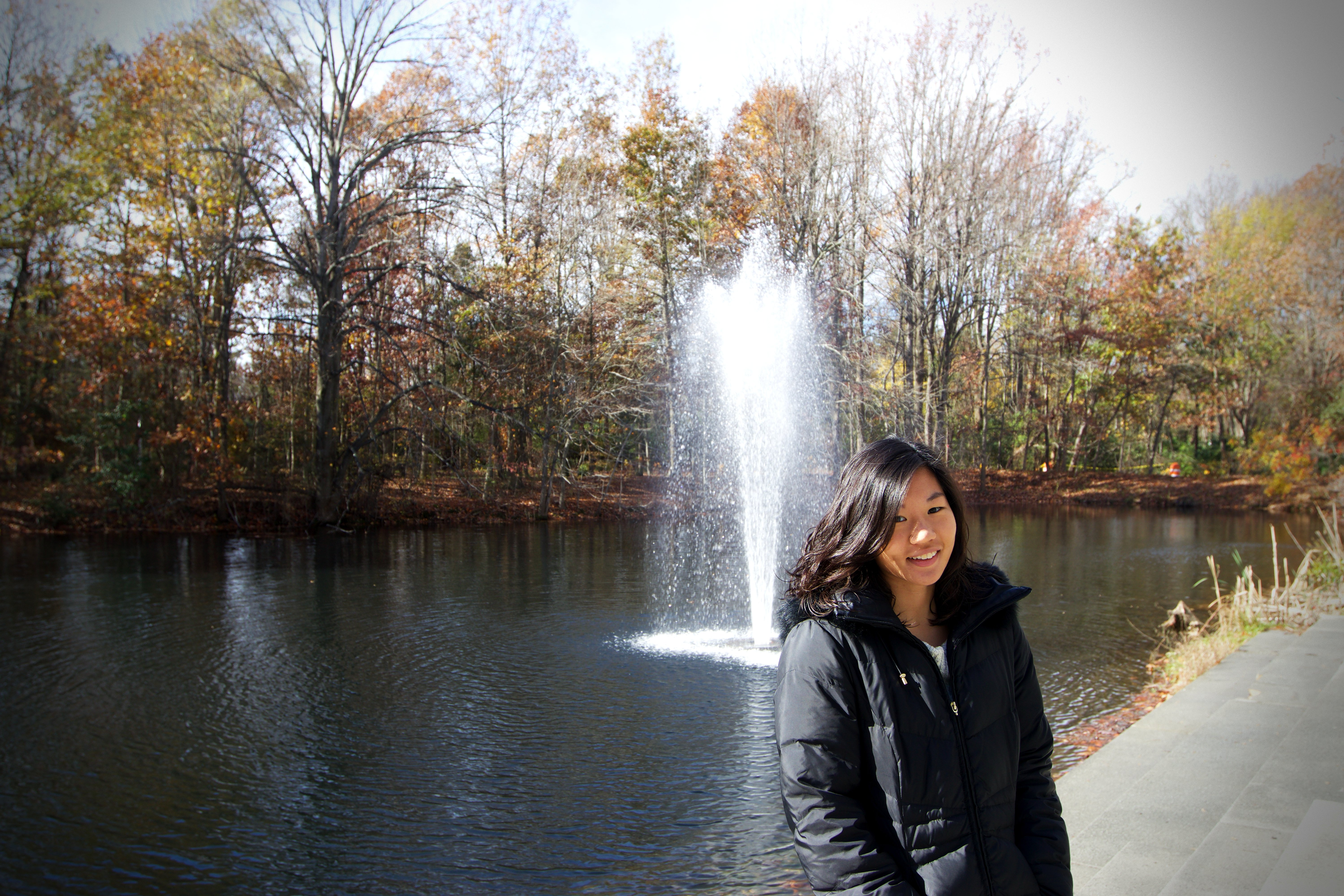 Rowan student, Jean Han, posing in front of the Engineering buildings fountain.