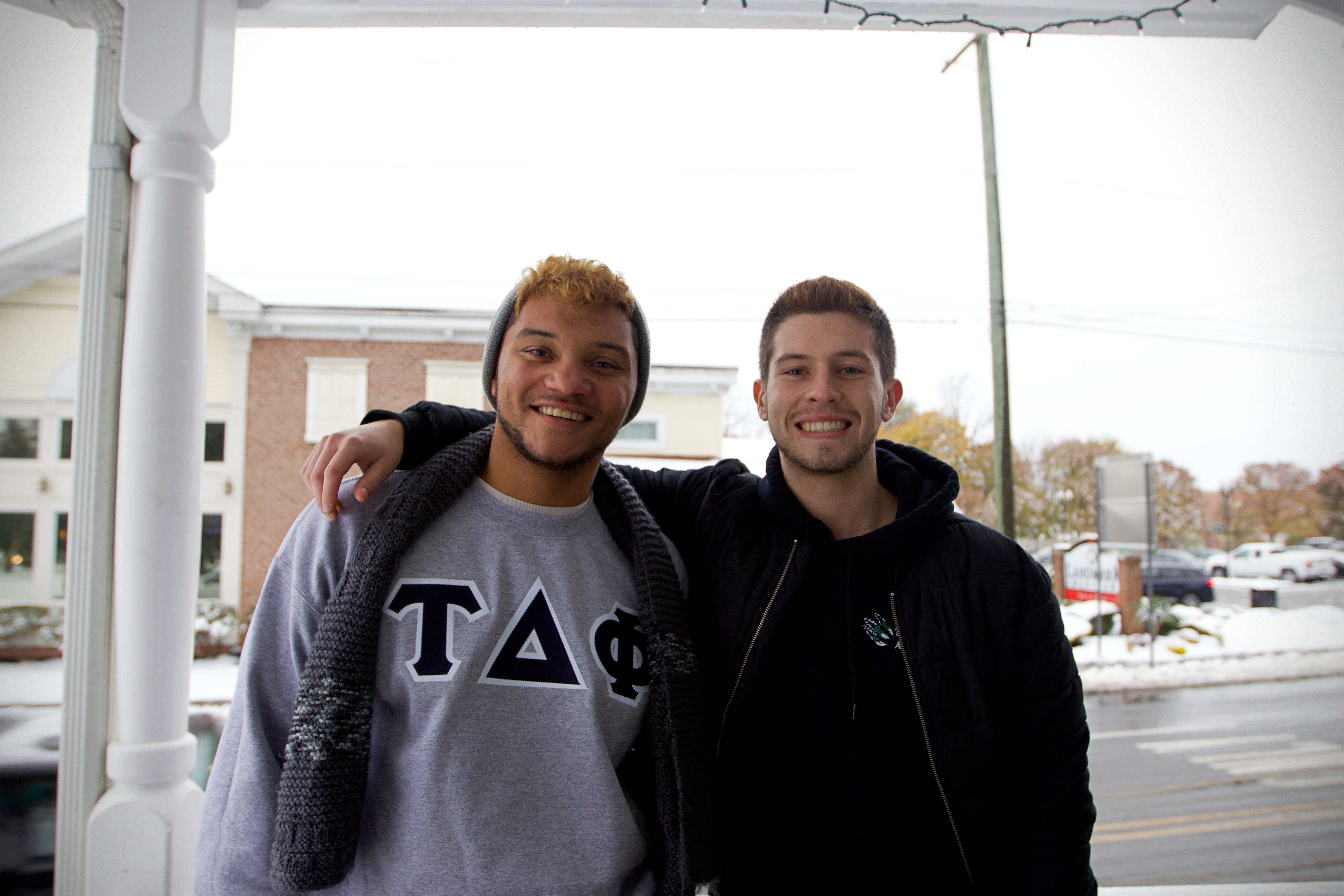 Joe (right) poses with his fraternity brother, James (left), outside their home.