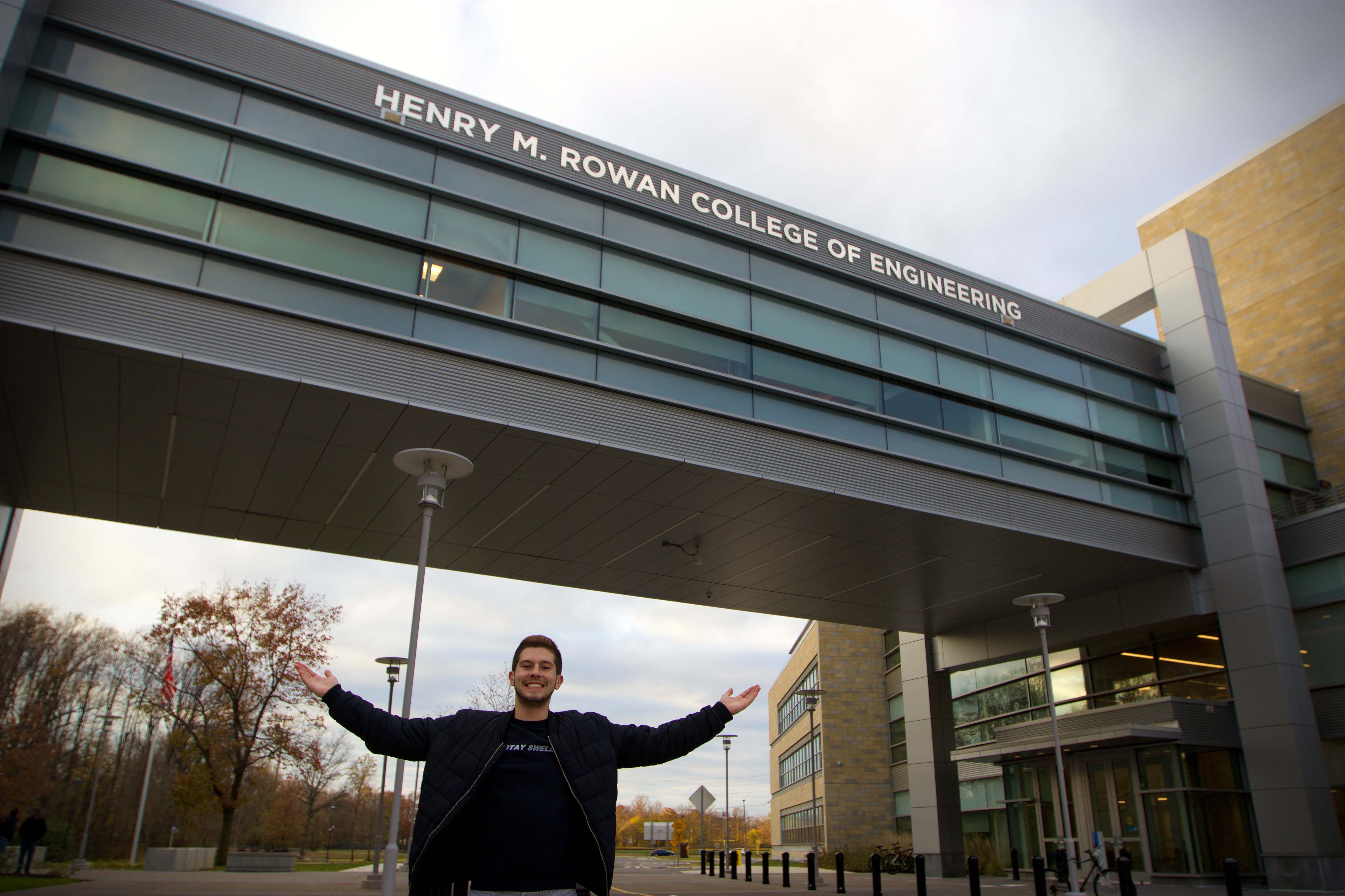 Joe proudly poses in front of the Henry M. Rowan College of Engineering building.