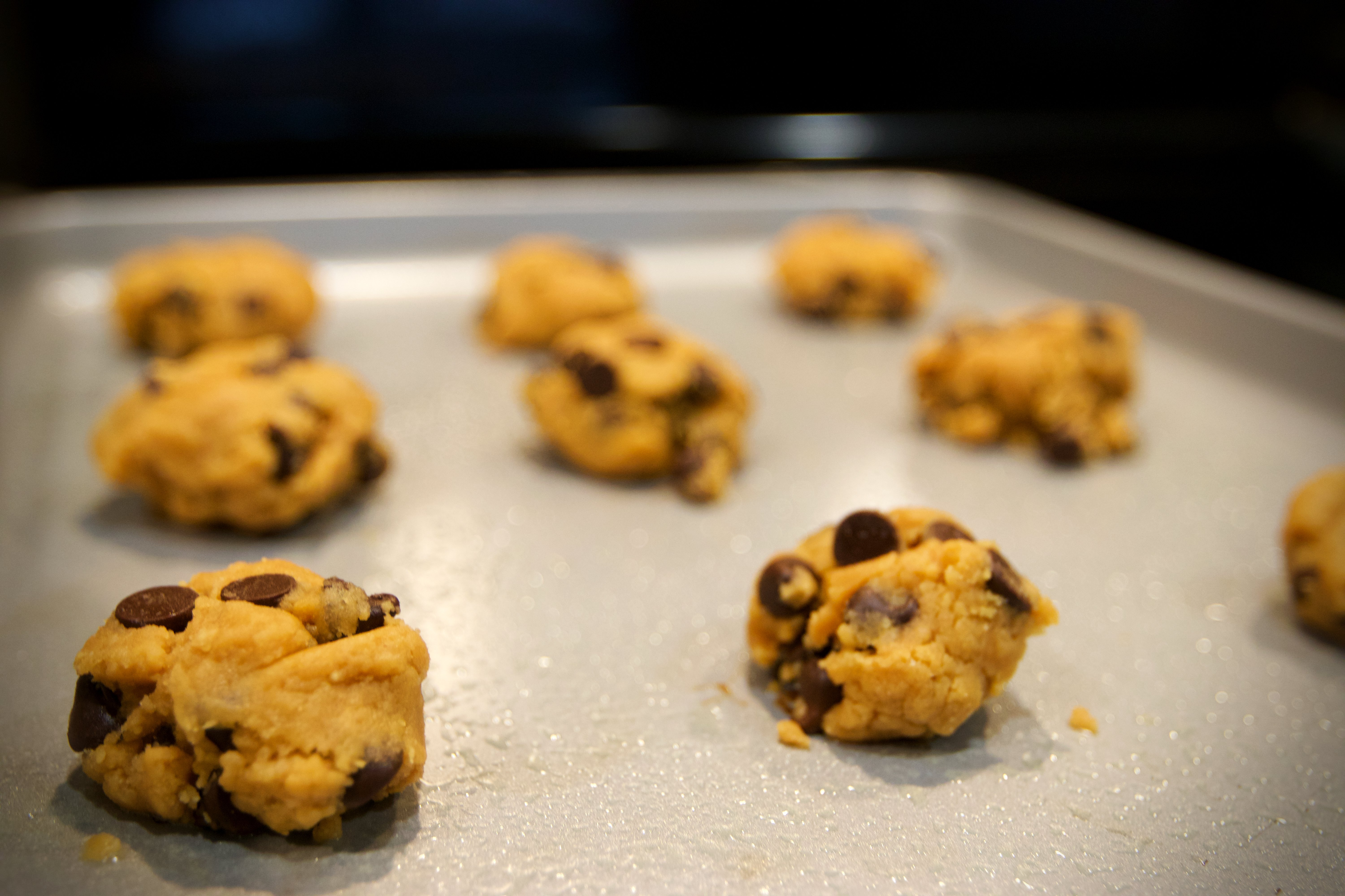Up-close picture of cookie dough laid out on cookie sheet.