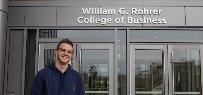 A Rowan student in a blue sweater standing outside the Business Building