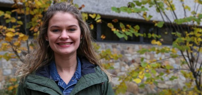 Sarah stands in front of autumn trees outside of Robinson Hall, smiling and wearing a green jacket