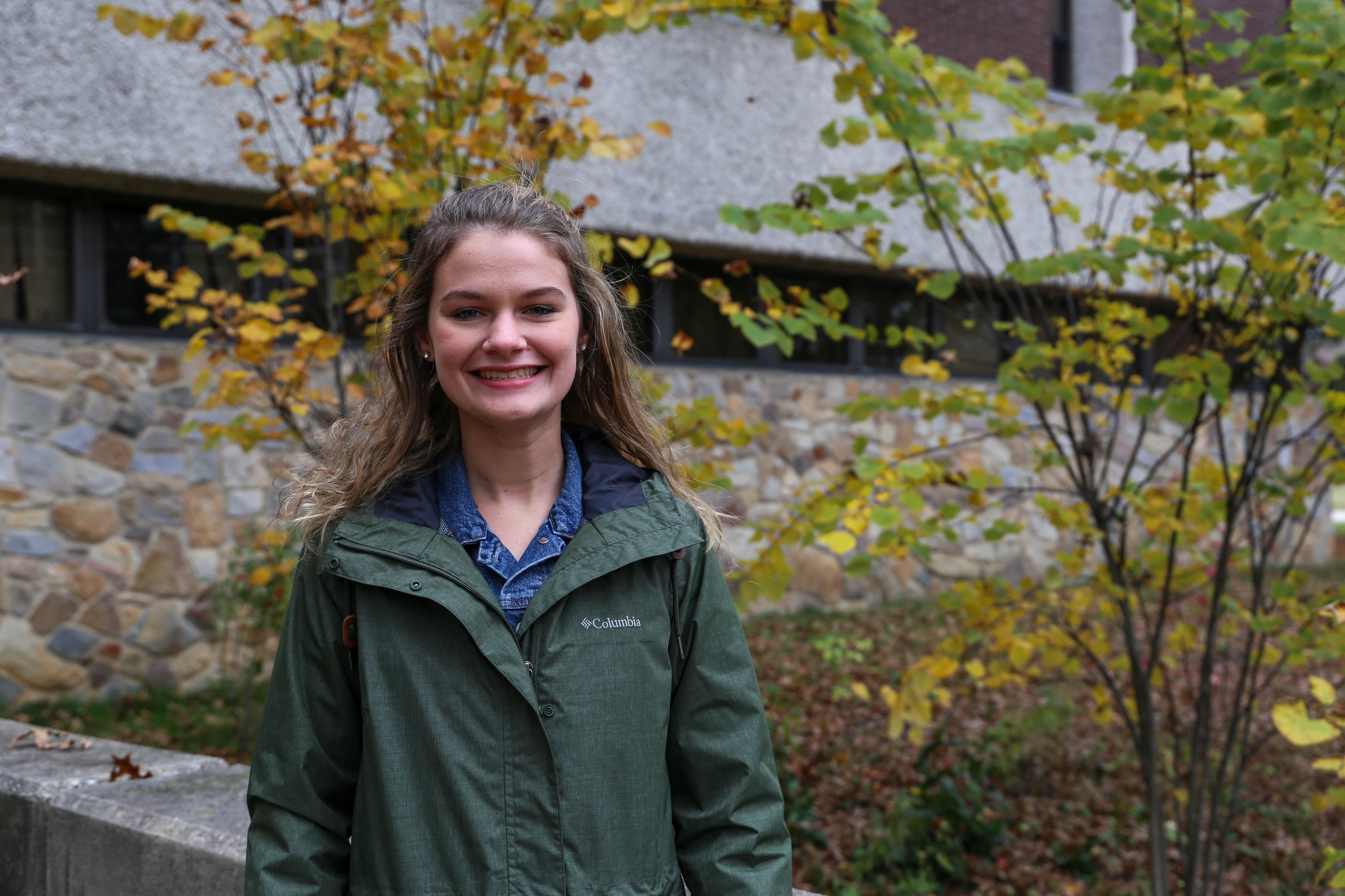 Transfer Student Sarah Burdhimo smiles outside of Robinson Hall, surrounded by fall foliage.