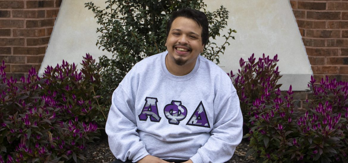 Victor sits on the brick area outside the student center while wearing a Greek Alpha Phi Delta sweatshirt