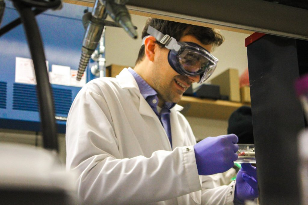 Analytical chemist James Grinias at Rowan University smiles while working in the lab