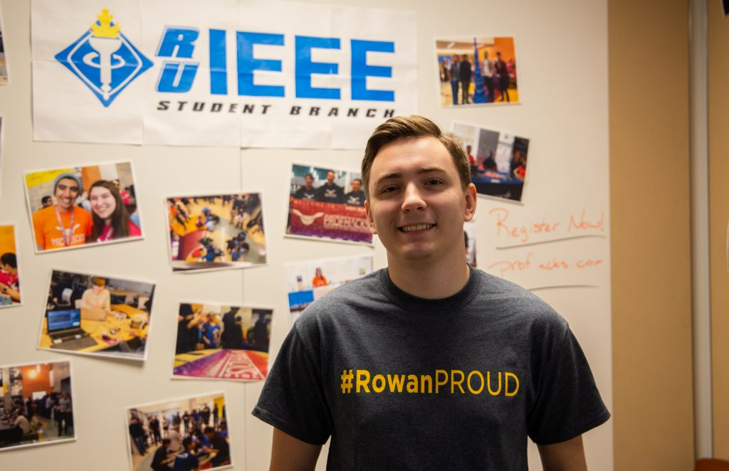 JD stands in front of theh Rowan Engineering IEEE sign wearing a #RowanPROUD t-shirt