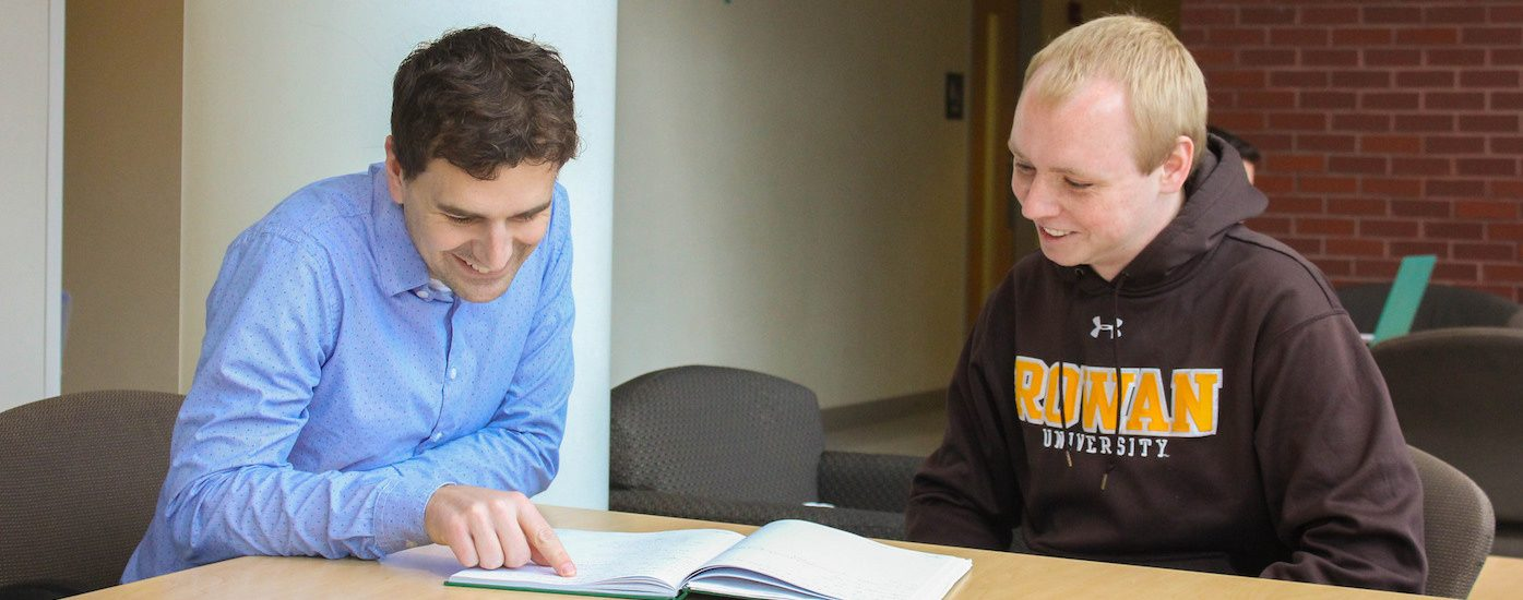 Analytical chemist James Grinias at Rowan University sits with a student