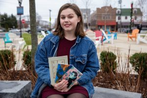 Rachel sitting on block at Town Square in Glassboro holding her books