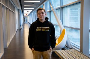 DJ standing in the walk way of the new engineering building on second floor in Rowan Engineering Hoodie
