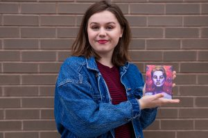 Rachel in jean jacket in front of brick background holding Avant literary magazine