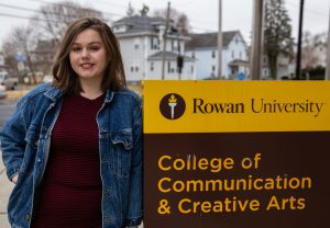 Rachel leaning on college of communications and creative arts sign outside High St on campus