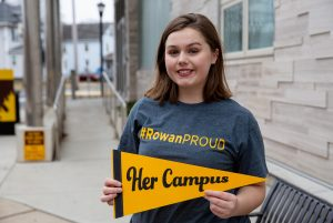Rachel in #ROWANproud shirt holding Her Campus pennant outside High St building