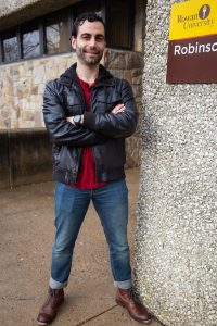 David standing in leather jacket outside Robinson Hall