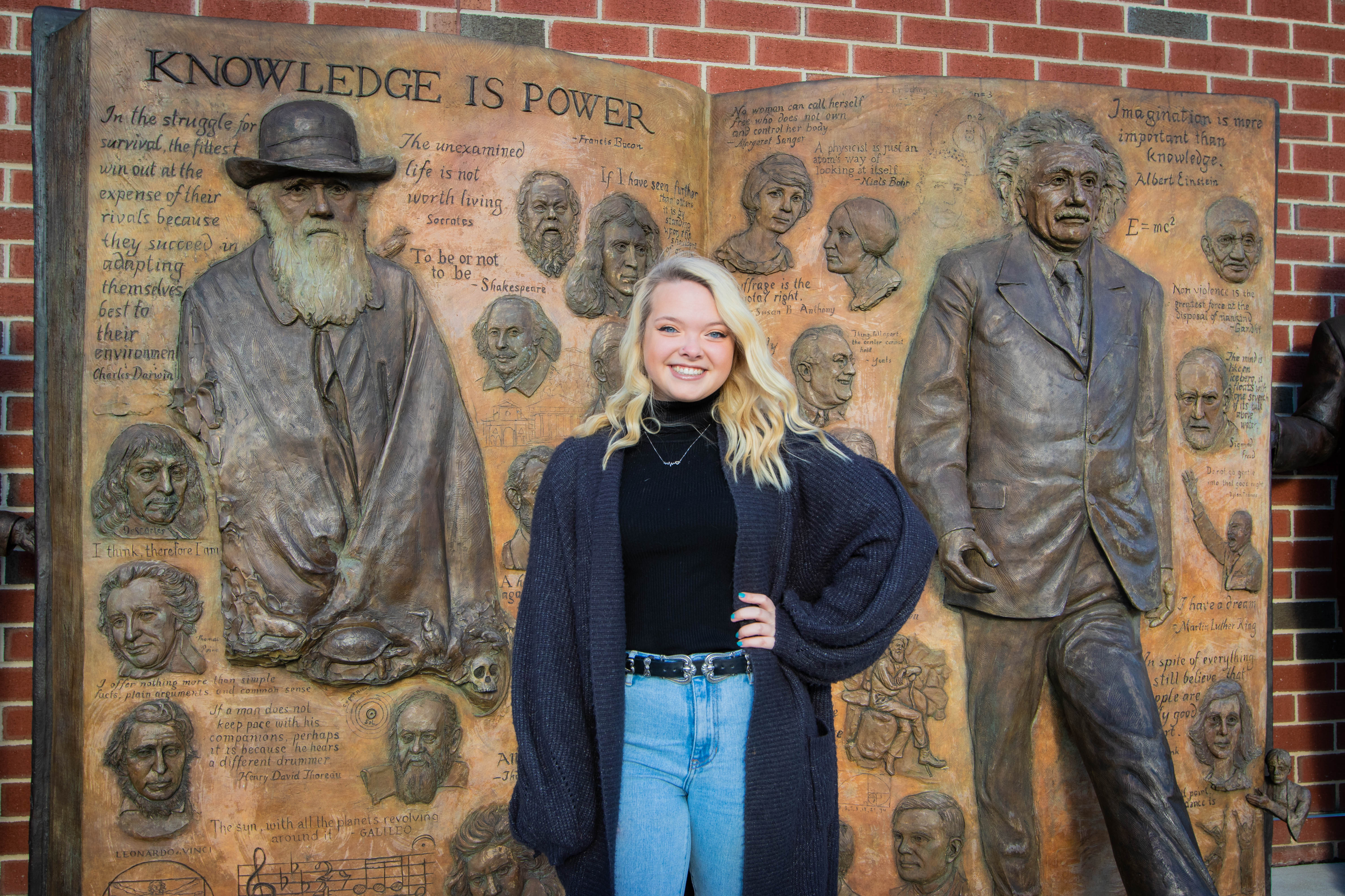 "Molly Moore posing in front of James Halls ""Knowledge is Power"" statue."