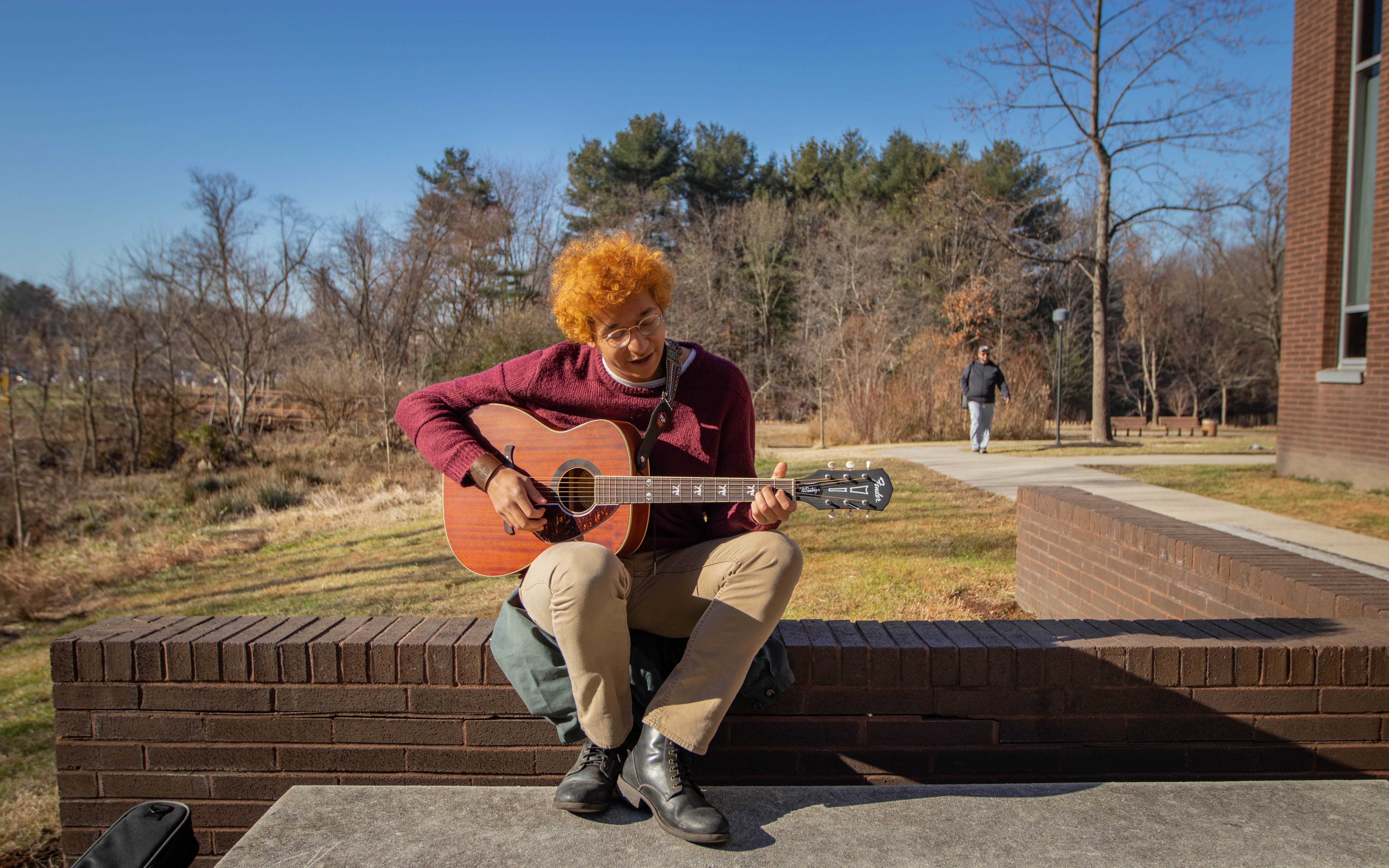 Luis playing his guitar on a bench outside of Wilson Hall.