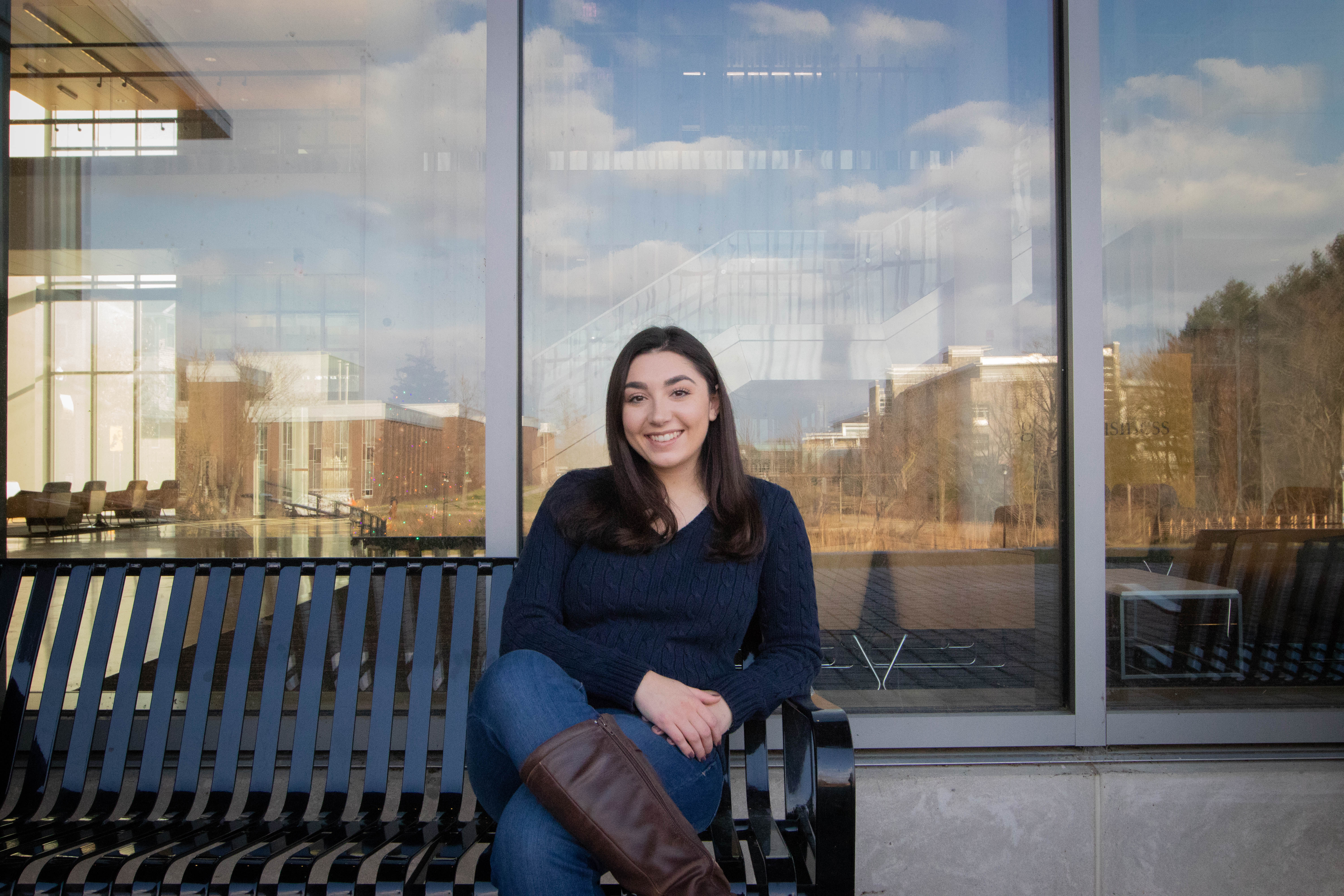 Sophia sitting outside Rowan's Rohrer College of Business building.