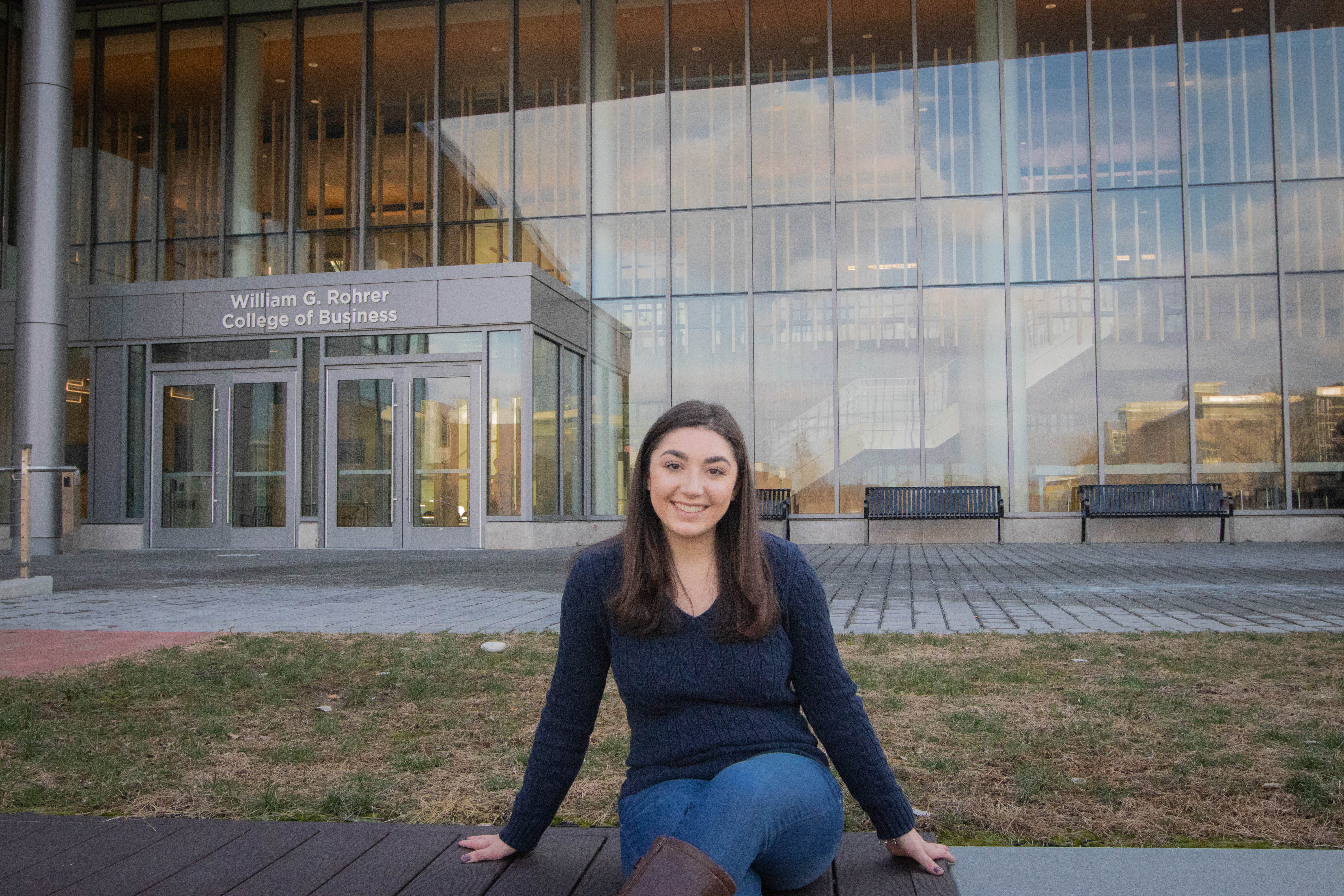 Sophia sitting on the steps of Rowan's Rohrer College of Business building.