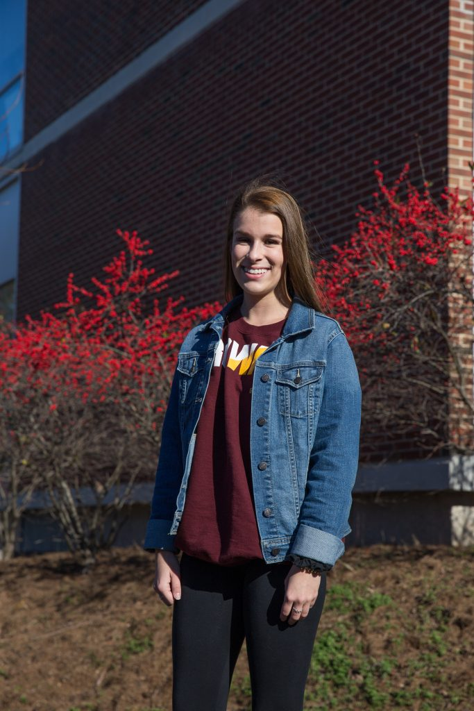 Skylar stands outside Savitz hall by a red berry tree