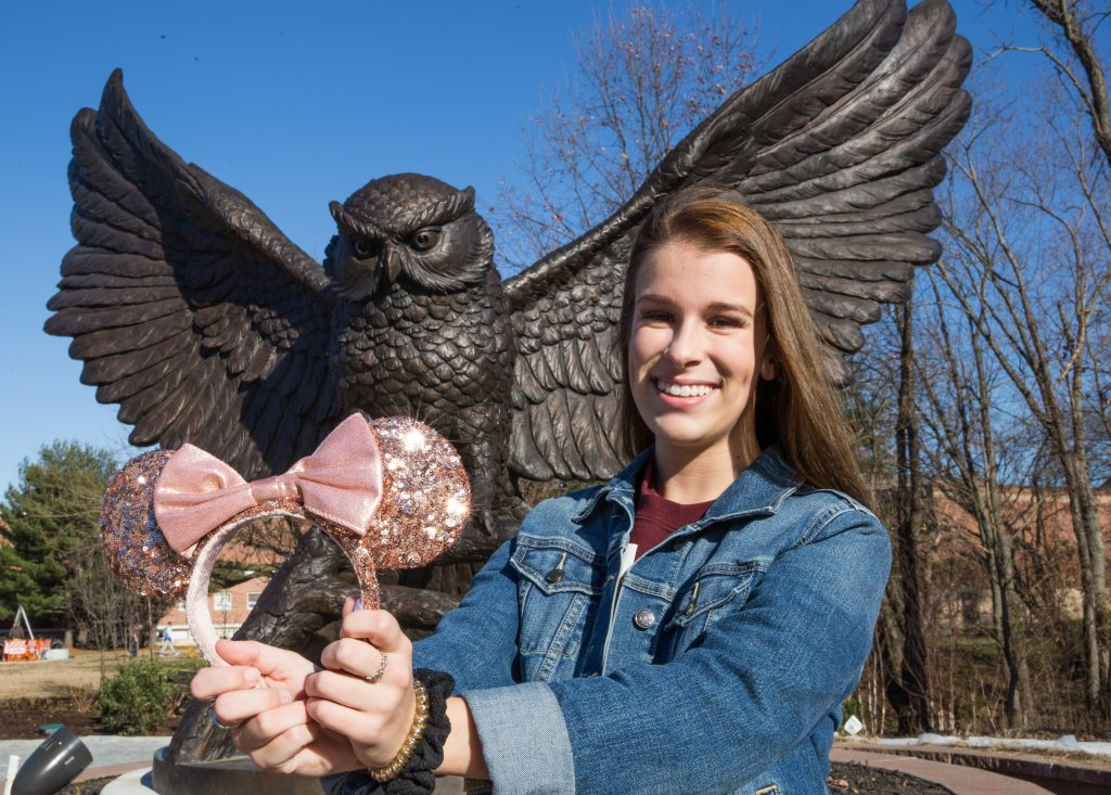 Skylar poses in front of the owl statue with a pair of pink minnie mouse ears