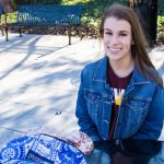 Skylar sits outside the student center at a solar panel powered bench