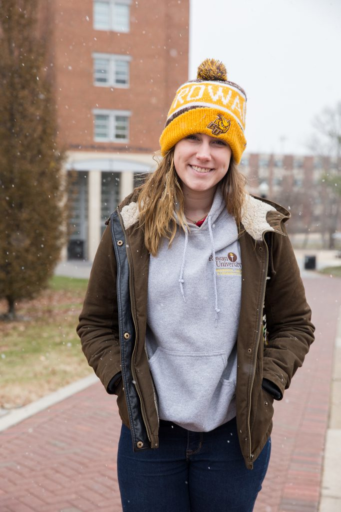 Cam stands outside the library in a Rowan university beanie