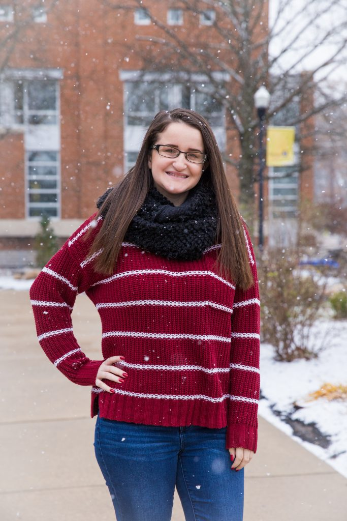 Lis stands outside Savitz Hall on a snowy day