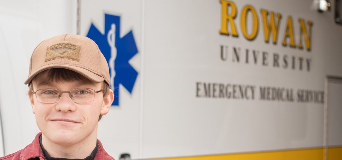 Young man standing in front of a white and yellow Rowan EMS vehicle