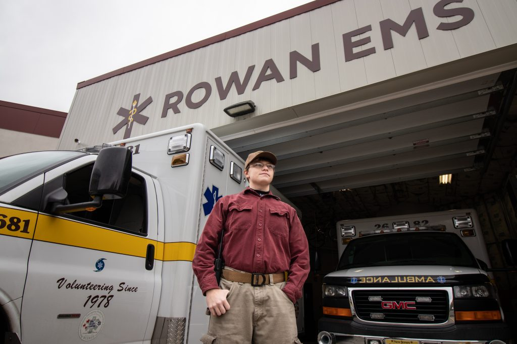 Young man in a red shirt and brown cap standing in front of Rowan's EMS vehicle garage